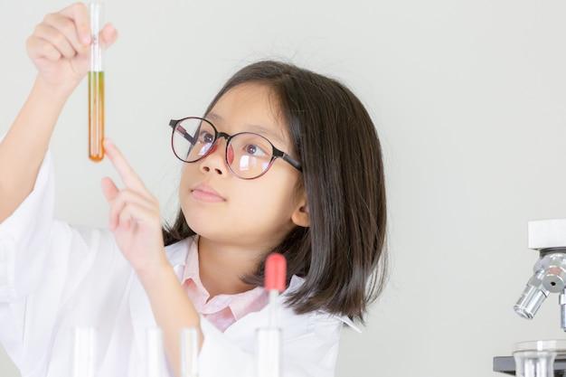 Kinderenwetenschap, het gelukkige meisje spelen die chemische experimenten doen in het laboratorium