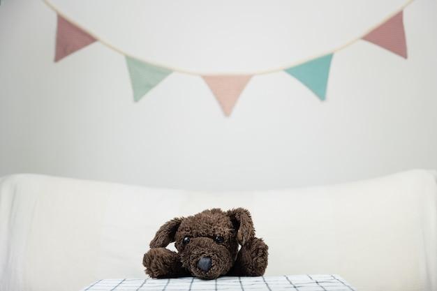 Kinderfeestje concept met pluizige speelgoedhond aan tafel. knuffeldier in minimalistische feestelijke achtergrond binnenshuis