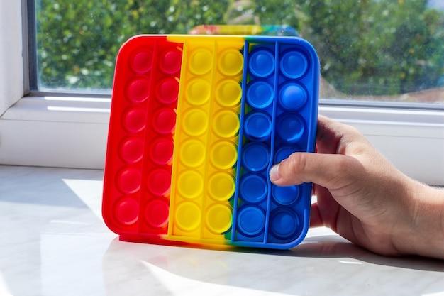 Kinderhand houdt een anti-stress speelgoed popit op de vensterbank.