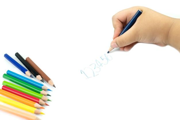 Kinderhand met potlood die engelse woorden met de hand schrijft op wit notitieblokpapier