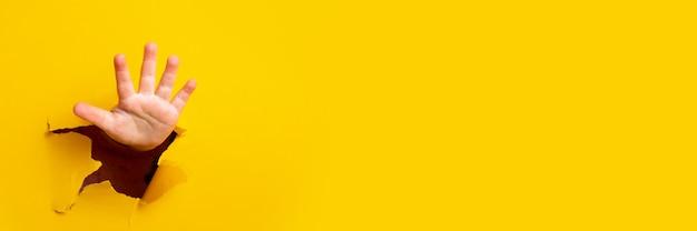 Kinderhand steekt uit een gat in een vel papier op een gele achtergrond. banner.