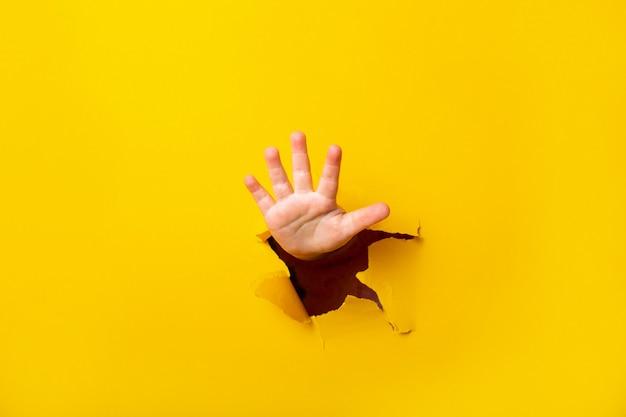 Kinderhand steekt uit een gat in een vel papier op een gele achtergrond. vijf vingerteken, exemplaarruimte.