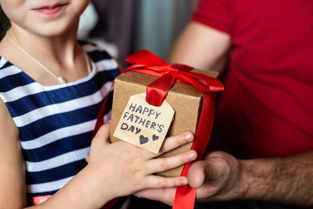 Kinderhanden geven een doos met een rode strik en een ansichtkaart