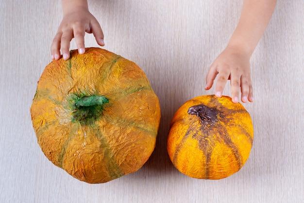Kinderhanden houden een zelfgemaakte oranje pompoen van papier-maché voor halloween op een tafel, flatley