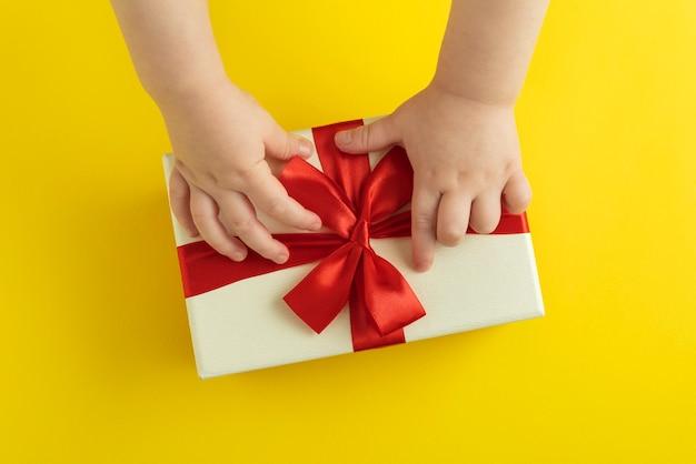 Kinderhanden maken de strik op de geschenkdoos los. bovenaanzicht.