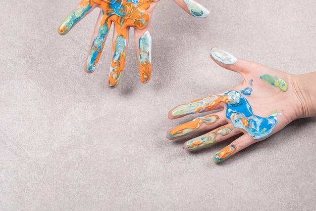 Kinderhanden met kleurrijke acryl olie mix