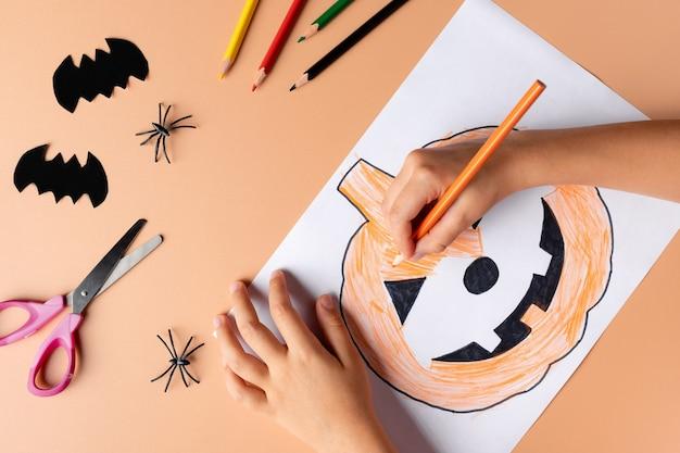 Kinderhanden schilderen pompoen met spookachtig gezicht halloween-voorbereiding kinderambachten