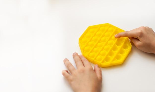 Kinderhanden spelen met geel pop-it-speelgoed op wit bureau