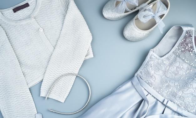 Kinderjurk, jas, schoenen en sieraden op een grijsblauwe achtergrond.