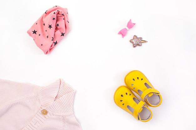 Kinderkleding en schoenen zijn neergelegd op een witte achtergrond bovenaanzicht. ruimte voor de tekst.
