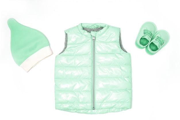 Kinderkleding in modieuze kleur. hoed, schoenen, gewatteerde jas