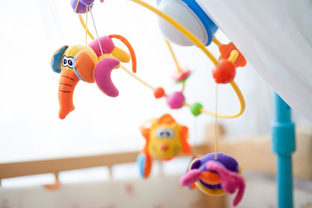 Kindermobiel boven het bed, draaiende carrousel met speelgoed
