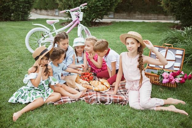 Kindermode concept. de groep tienerjongens en meisjes die bij groen gras bij park zitten.
