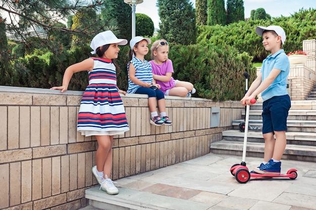 Kindermode concept. de groep tienerjongens en meisjes die bij park stellen. kleurrijke kinderkleding, lifestyle, trendy kleurenconcepten.