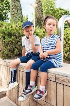 Kindermode concept. de tienerjongen en het meisjeszitting bij park. kleurrijke kinderkleding, lifestyle, trendy kleurenconcepten. kaukasische modellen