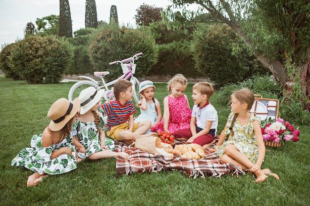 Kindermode concept. groep tiener jongens en meisjes zitten op groen gras in het park