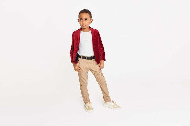 Kindermode, stijl, schoonheid en etniciteit concept. geïsoleerde volledige lengte shot van zelfverzekerde ernstige afro-amerikaanse schooljongen poseren tegen kopie ruimte achtergrond