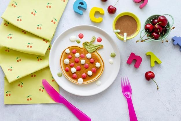 Kinderpannenkoekontbijt in de vorm van een grappige aardbei