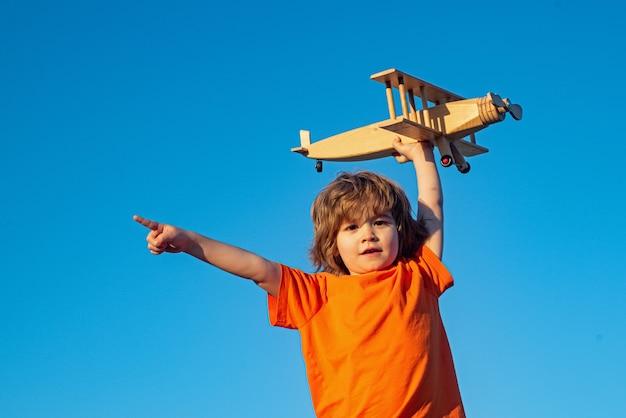 Kinderpiloot die kopieerruimte toont of wijst. kleine jongen met houten vliegtuig. jongen met vliegtuig op lucht, hemelachtergrond.