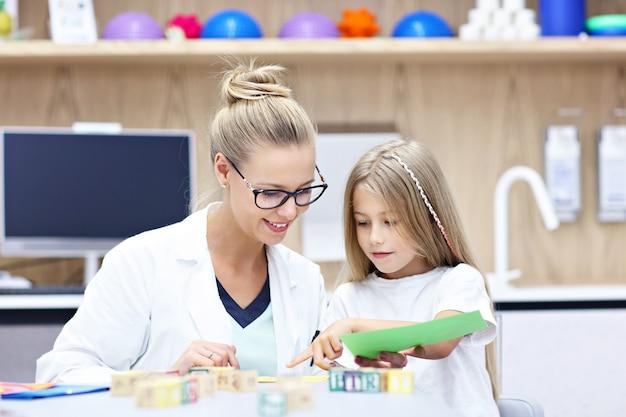 Kinderpsycholoog die werkt met een jong meisje op kantoor