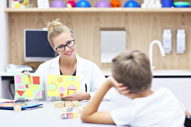Kinderpsycholoog die werkt met jonge jongen op kantoor