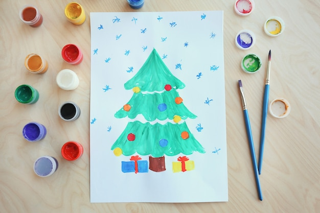 Kinderschilderij van kerstboom met cadeautjes op tafel