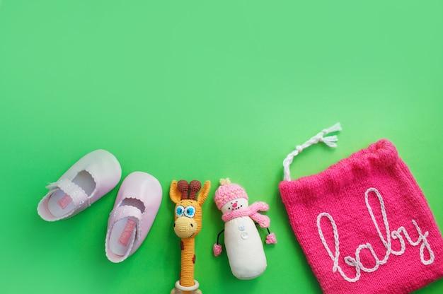 Kinderschoenen liggen op een lichtgroene bovenaanzicht als achtergrond. ruimte voor de tekst. babyslofjes.