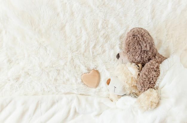 Kinderspeelgoed slaapt onder de deken. kopie ruimte. selectieve aandacht.