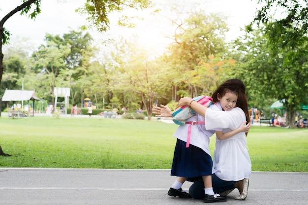 Kinderstudent in moeders handen om haar te knuffelen na terug naar school.