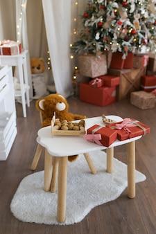 Kindertafel met een zachte beer op de achtergrond van een kerstboom en cadeautjes