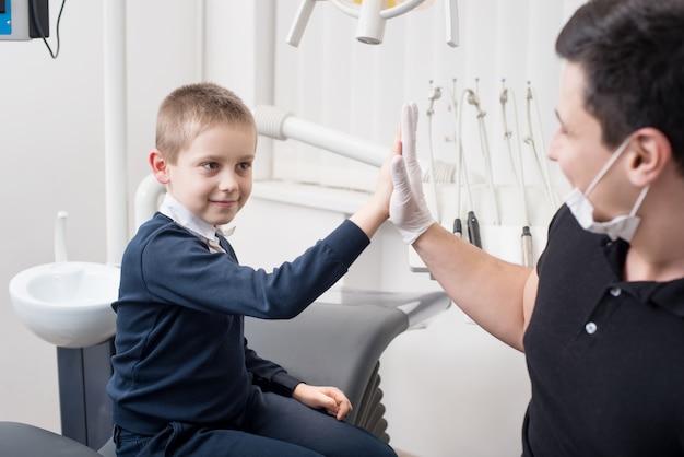 Kindertandarts geeft vijf jonge jongens, feliciteer de patiënt voor een succesvolle behandeling