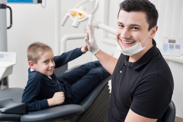 Kindertandarts schudden handen met jonge jongen, feliciteer patiënt met een succesvolle operatie in de tandartspraktijk