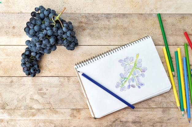 Kindertekening, druiven en kleurpotloden. houten tafel. bovenaanzicht