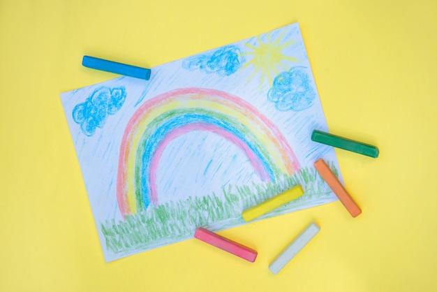 Kindertekening met kleurrijke regenboog op een stuk papier