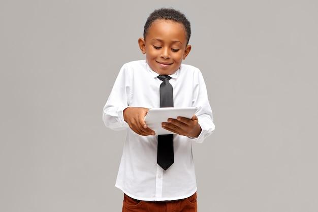 Kindertijd, moderne technologie en verslaving. schattige afro-amerikaanse schooljongen verslaafd aan elektronische gadgets met behulp van digitale tablet om videogames te spelen, gelaatsuitdrukking geabsorbeerd