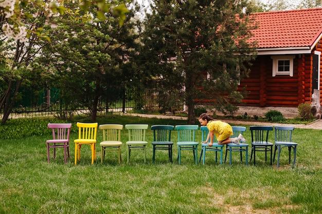 Kinderverjaardagsfeestje buiten het feestvarken kruipt langs een rij kleurrijke stoelen die wachten op...