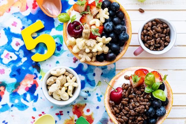 Kinderverjaardagsontbijtschalen met ontbijtgranen en bessen