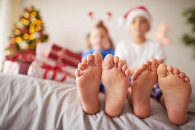 Kindervoeten in het bed met kerstmis