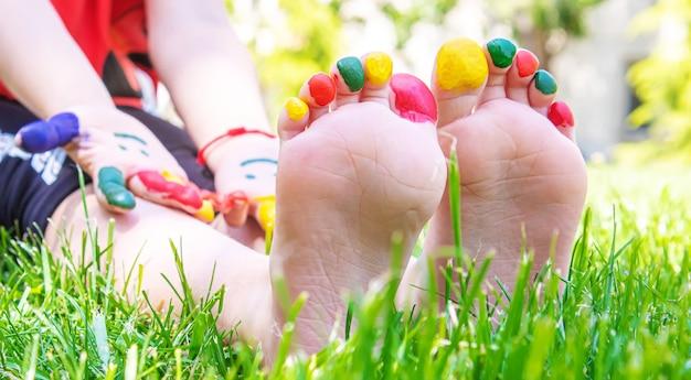 Kindervoeten met een patroon van verfglimlach op het groene gras. selectieve aandacht. natuur.