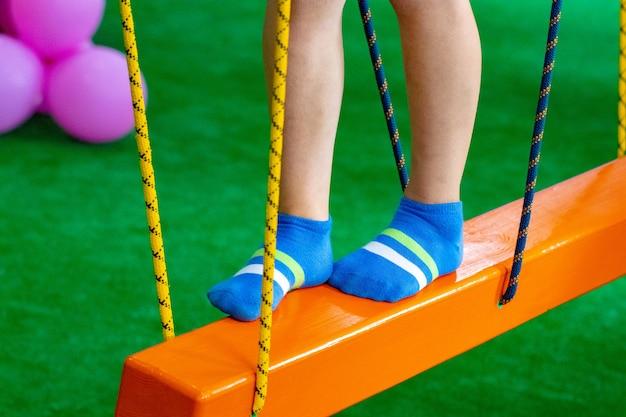 Kindervoeten op de speelplaats met schommelbrug. Premium Foto