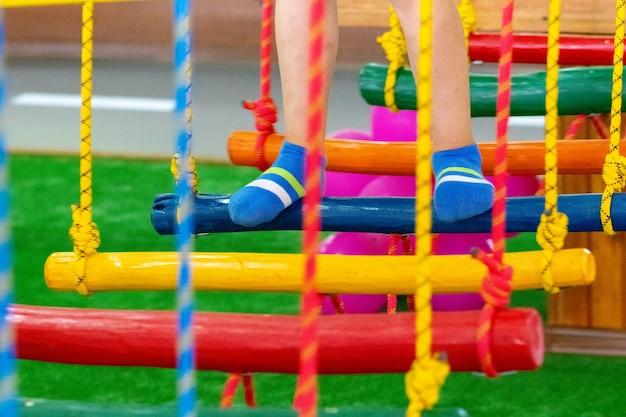 Kindervoeten op de speelplaats met schommelbrug.