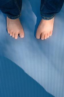 Kindervoeten op een blauw tapijt voor yogabeoefening
