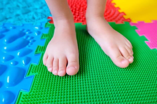 Kindervoeten op orthopedische matten, ter voorkoming van platvoeten.