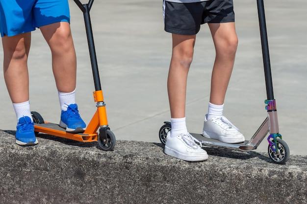 Kindervoeten op veelkleurige scooters, twee kinderen, close-up, buitenentertainment
