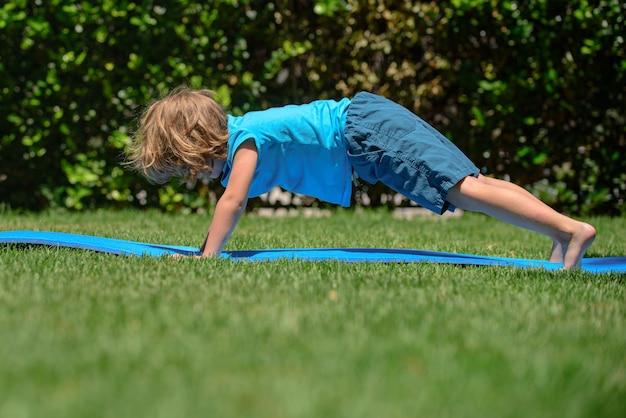 Kinderyoga kind doet yoga-oefeningen jongensyoga buiten