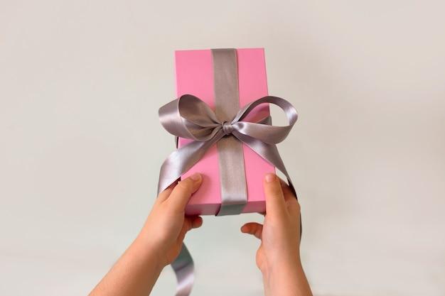 Kindhanden die een roze gift met zilveren lint oppakken