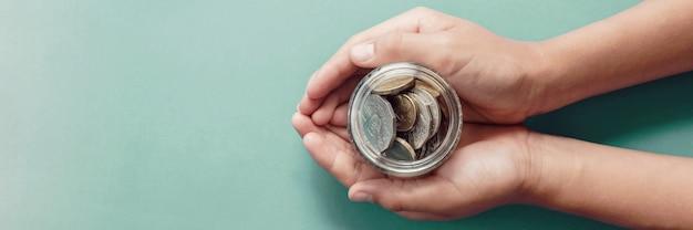 Kindhanden die geldkruik, schenking, besparing, liefdadigheid, het planconcept van familiefinanciën houden