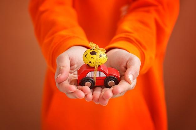 Kindhanden die paasei op auto op oranje achtergrond houden. vrolijk pasen-concept.