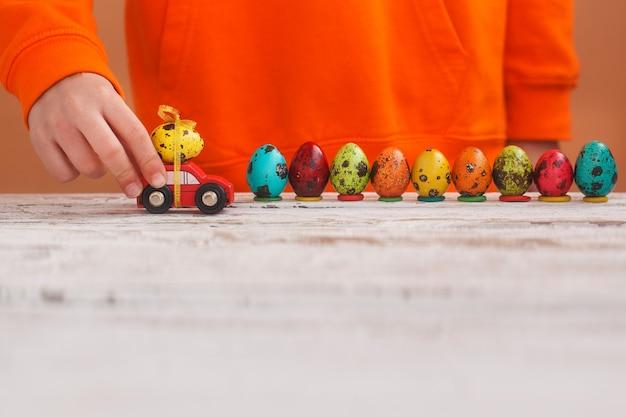 Kindhanden die paasei op auto op oranje achtergrond spelen. vrolijk pasen-concept.