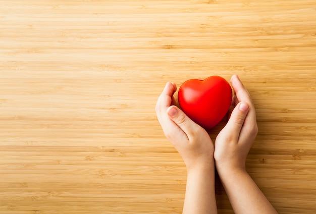 Kindhanden die rood hart, gezondheidszorg, schenken en familieverzekeringsconcept houden
